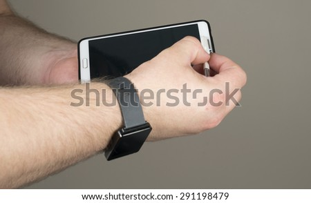 A man wearing a smart watch while holding and using a smart phone. - stock photo