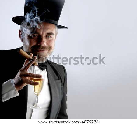 A man wearing a smoking holding a glass and cigar, against a gray background - stock photo