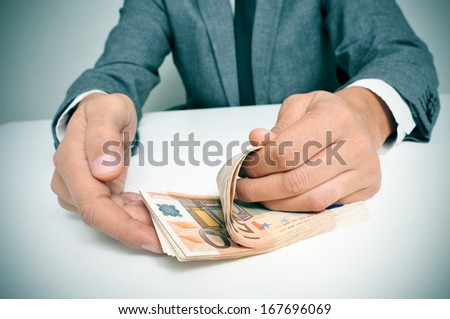 a man wearing a suit sitting in a desk counting euro bills