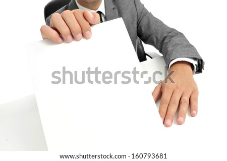 a man wearing a suit sitting in a desk holding a blank signboard with a copy-space - stock photo