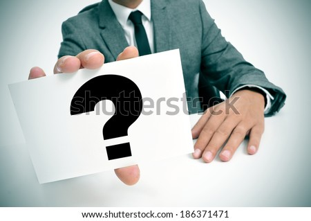 a man wearing a suit sitting in a desk holding a signboard with a question mark - stock photo