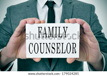 a man wearing a suit sitting in a desk with a desktop nameplate in front of him with the word family counselor - stock photo