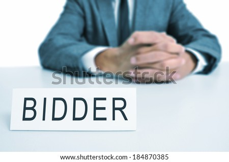 a man wearing a suit sitting in a desk with a desktop nameplate in front of him with the word bidder - stock photo