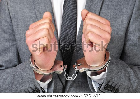 a man wearing a suit, with handcuffs in his wrists - stock photo