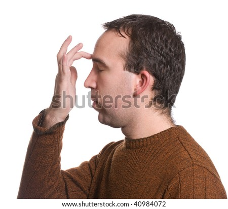 "A man wearing a sweater is doing the ""emotional freedom technique"" by tapping on his forehead, isolated against a white background - stock photo"
