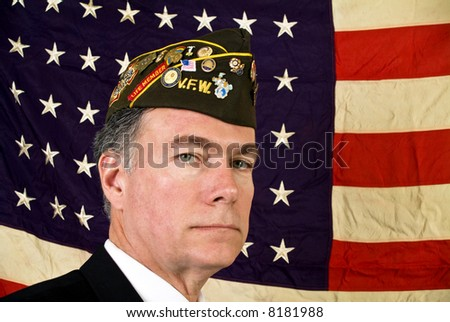A man wearing a V.F.W. cap standing in front of an old faded 48 star American Flag. - stock photo