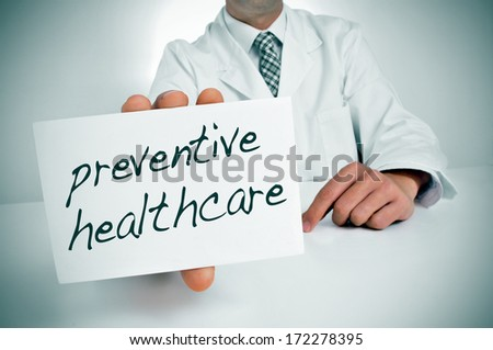 a man wearing a white coat showing a signboard with the text preventive healthcare written in it - stock photo