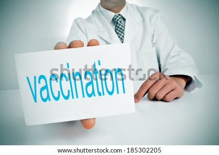a man wearing a white coat showing sitting in a desk a signboard with the word vaccination written in it - stock photo