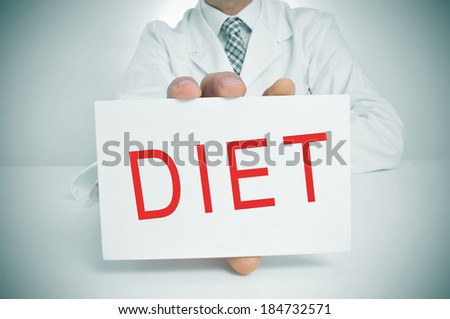 a man wearing a white coat sitting in a desk showing a signboard with the word diet written in it - stock photo