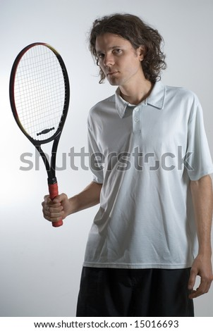 A man, wearing a white polo, holds a tennis racket, looking angrily. Vertically framed shot. - stock photo