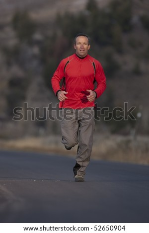 A man wearing athletic clothing is jogging down a road with a high desert landscape in the background. Vertical shot. - stock photo