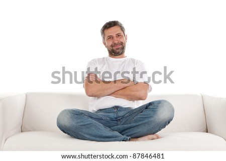A man wearing casual jeans and t-shirt sits relaxing on a white sofa with his arms and legs crossed. - stock photo