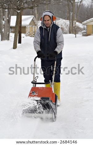A man wearing ear protection clears his driveway with snowblower. - stock photo