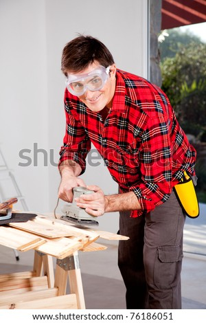 A man wearing saftey goggles using an electric hand sander - stock photo