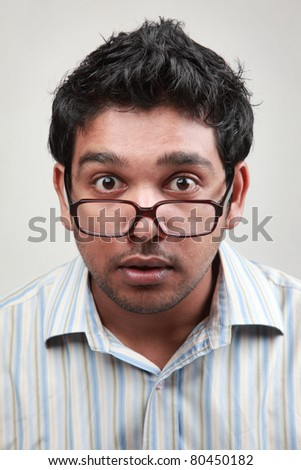 A man wearing spectacle shows the expression of excitement - stock photo