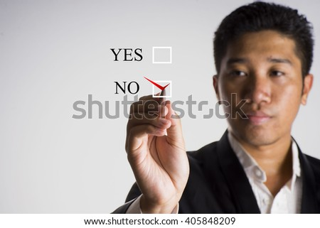 A man wearing tuxedo writing checklist with the options of yes or no on screen, select focus - business concept - stock photo