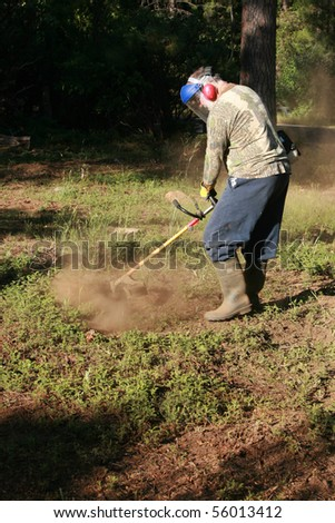 a man wears his protective gear as he cuts brush with his weed wacker - stock photo