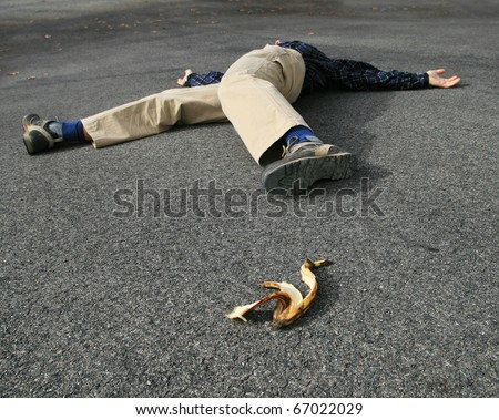 a man who had an accident when he slipped on a banana peel lies on the ground - stock photo