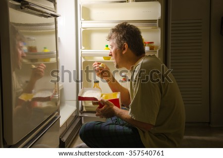 A man who has nighttime sleep-related eating disorder sleep eating as he sits in front of a refrigerator eating ice cream out of carton, oblivious to everything around him as he is actually sleeping. - stock photo