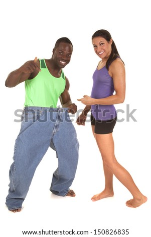 A man who is holding out his pants with a smile on his face he has lost weight. - stock photo
