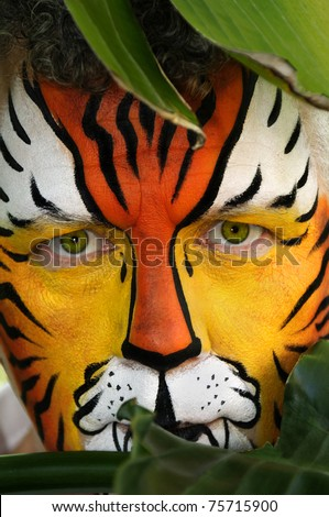 A man who's face is painted like a tiger, peeking behind tropical leaves. - stock photo