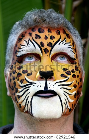 A man who's face is painted looking up. - stock photo