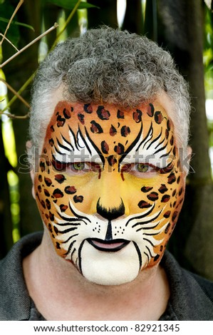 A man who's face is painted to look like a leopard. - stock photo
