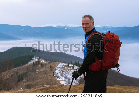A man with a backpack over the clouds - stock photo