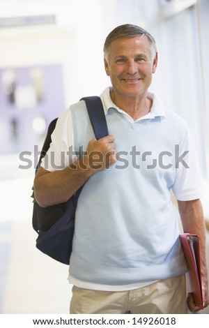 A man with a backpack standing in a campus corridor