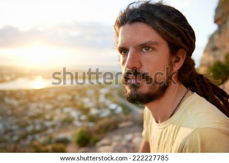 A man with a beard and dreadlocks sitting on a mountain appreciating the view during sunset - stock photo