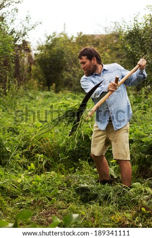 a man with a beard mowing grass with a scythe - stock photo