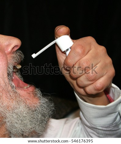 A man with a beard splashes spray into the mouth. Treatment of bad breath. Sore throat. Preventing colds and flu