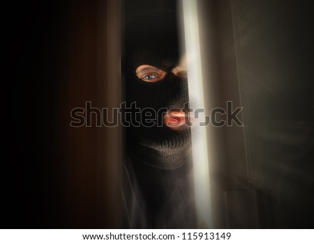 A man with a black mask is breaking into a home and the focus is in his eye. Use it for a security or danger concept. - stock photo