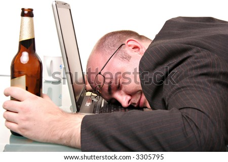 A man with a bottle of beer fallen to sleep on his computer. Isolated on white - stock photo