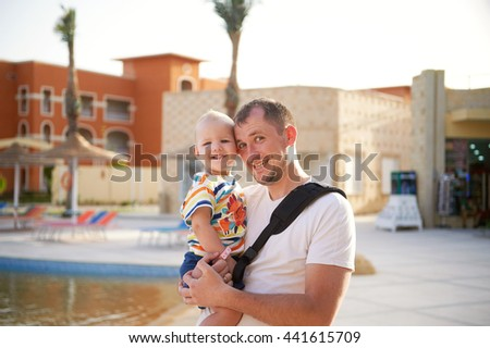A man with a boy holding a boy in her arms looking at the camera smiling happy on vacation - stock photo