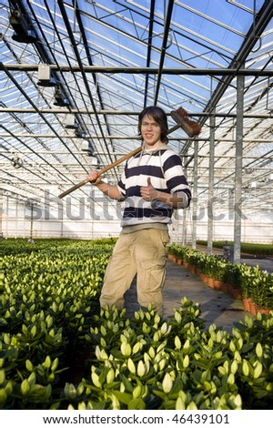 A man with a broom in his hand giving a thumbs-up inside a glasshouse, surrounded by potted plants - stock photo