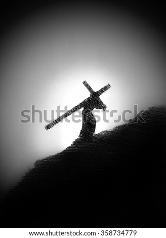 a man with a cross on his shoulder at dusk - stock photo