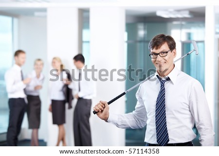 A man with a golf club against a background of office workers - stock photo