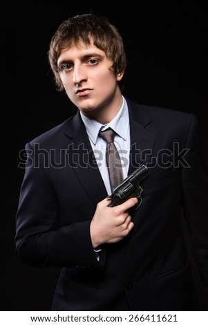 a man with a gun in studio. weapons, crime - stock photo