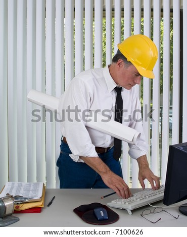 A man with a hardhat on standing in front of a computer as if checking some data. - stock photo
