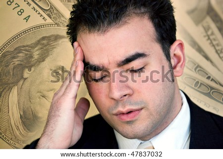A man with a headache from all of the stress of his financial problems. - stock photo