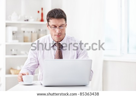 A man with a laptop and a cup in the kitchen