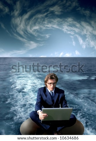 a man with a laptop on the water - stock photo
