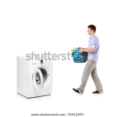 A man with a laundry basket going towards a washing machine isolated on white background - stock photo