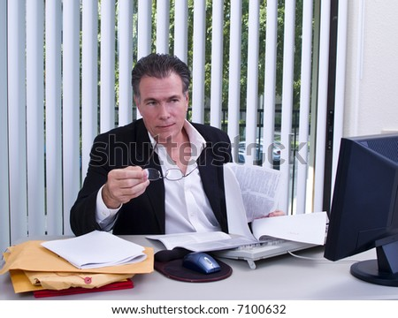 A man with a legal size document in his hands acting as if he is telling someone something. - stock photo