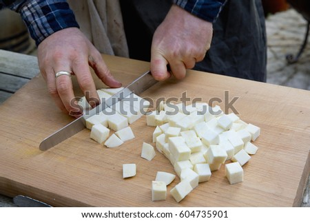 A man with a long knife chopping celeriac into cubes on a chopping board