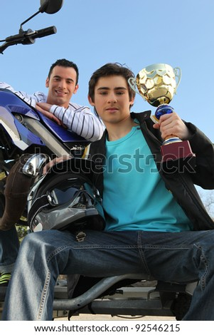 A man with a motorcycle and a trophy. - stock photo