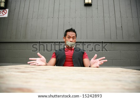 a man with a one dollar bill taped over his mouth expresses frustration with the us economy - stock photo