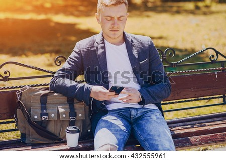 A man with a phone and tablet computer running outdoors on a sunny day - stock photo