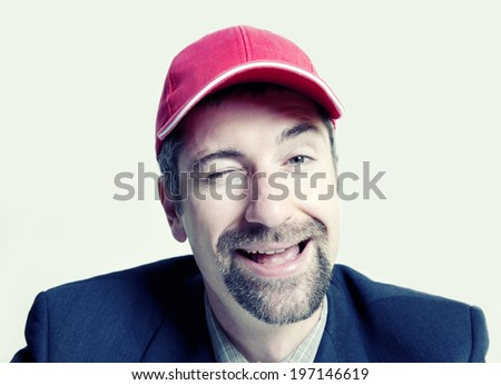 A man with a red cap winking and smiling. - stock photo